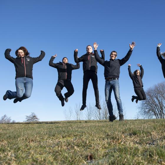 personal från klingbergs hoppar i luften på en gräsmatta