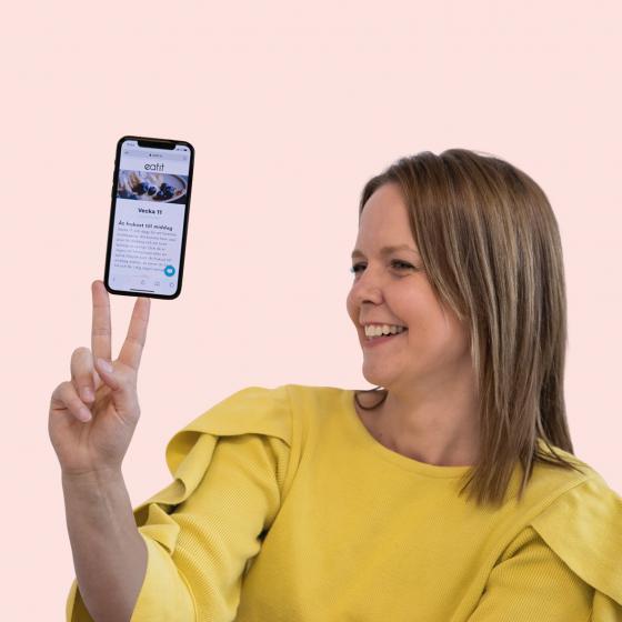 Kvinna balanserar sin mobil, med Eatit Hälsoguide på skärmen.