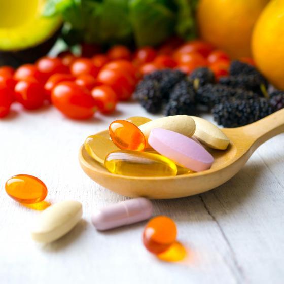 Färgglada piller bland frukt och grönsaker.