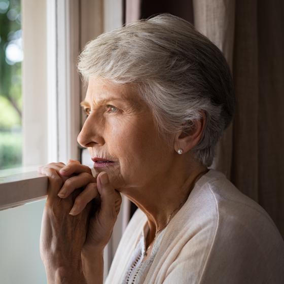 Äldre kvinna tittar ut genom ett fönster