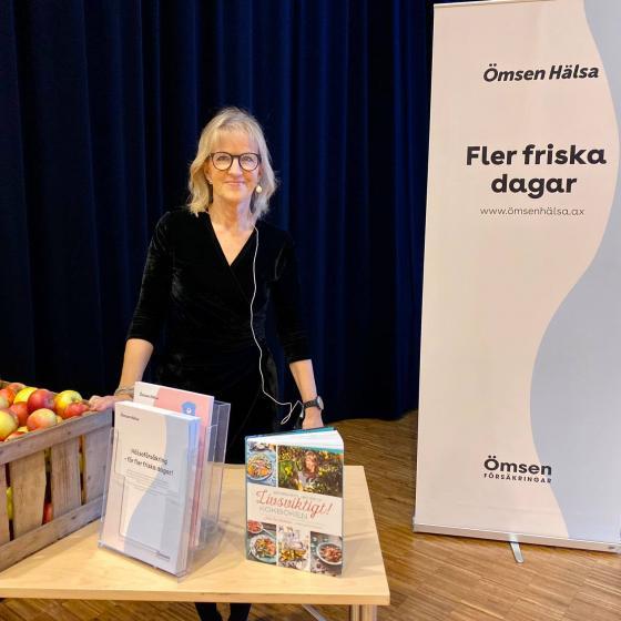 Mai-Lis Hellenius står bakom ett bord vid föreläsningstillfället. På bordet finns broschyrer och äpplen.