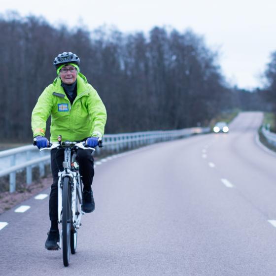 Marita cyklar vid vägkanten på en trafikerad väg en mulen dag.