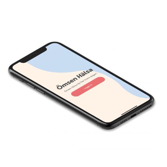 Mobiltelefon med Ömsen Hälsa appen i displayen.