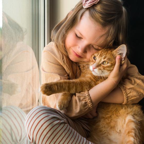 Liten flicka kramar om en katt.