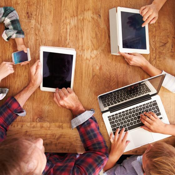 Familj sitter vid ett bord och alla har varsin mobiltelefon eller surfplatta.