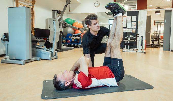 Naprapat Kristoffer Weckström hjälper en man med en övning