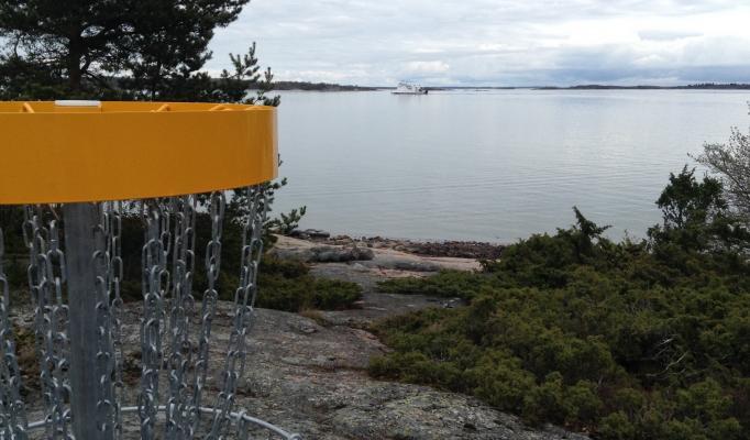 Korg till frisbeegolfbanan ute på Lappo. Skärgårdsfärja i bakgrunden.