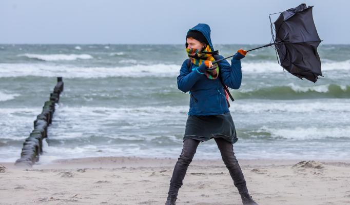 Kvinna står och håller i ett paraply på en strand i stormigt väder