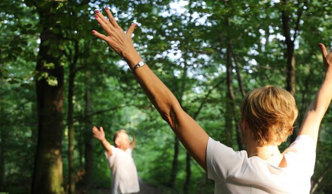 Kvinna och man sträcker upp sina händer i skog