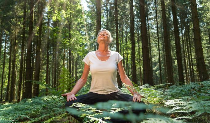 Kvinna sitter i skräddarställning i skogen