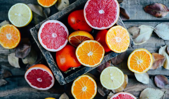 Uppskurna, halverade apelsiner och grapefrukter