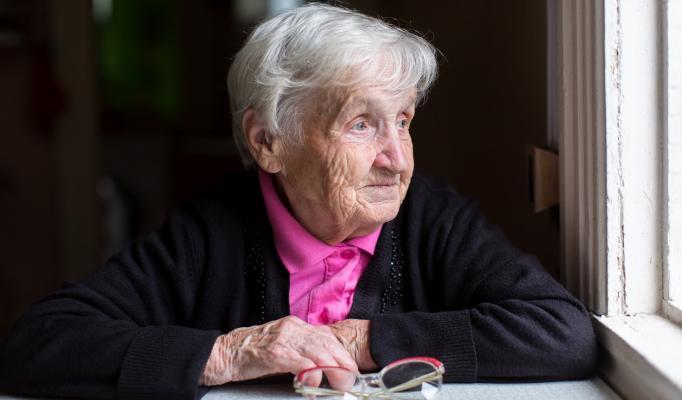 Äldre kvinna sitter vid ett bord