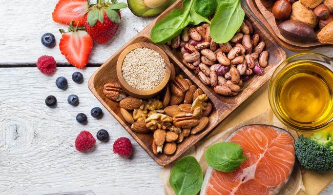 Bild på olika livsmedel. Jordgubbar, lax, avocado, nötter, blåbär och olivolja.